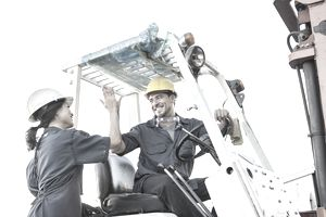 Warehouse worker high fiving colleague on forklift truck
