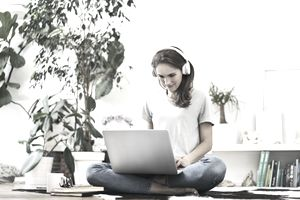 Young woman at home sitting on the floor using laptop and listening to music