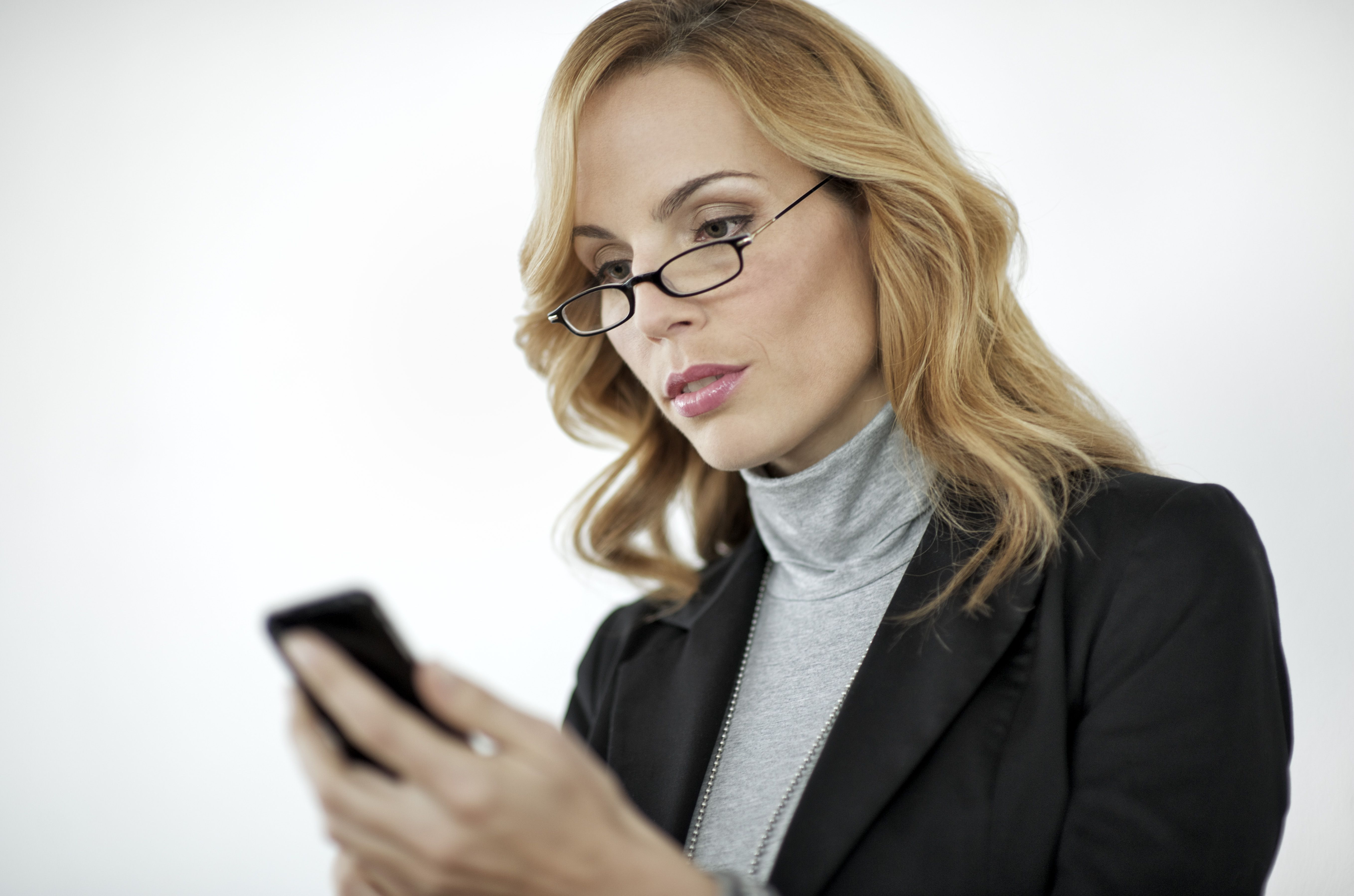 Businesswoman checks voice mail on mobile phone