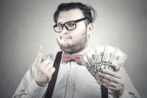 man with pinocchio nose and a handful of cash