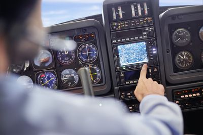 Male pilot using navigational instruments in airplane cockpit