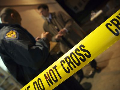 A police detective investigating a case at a crime scene with