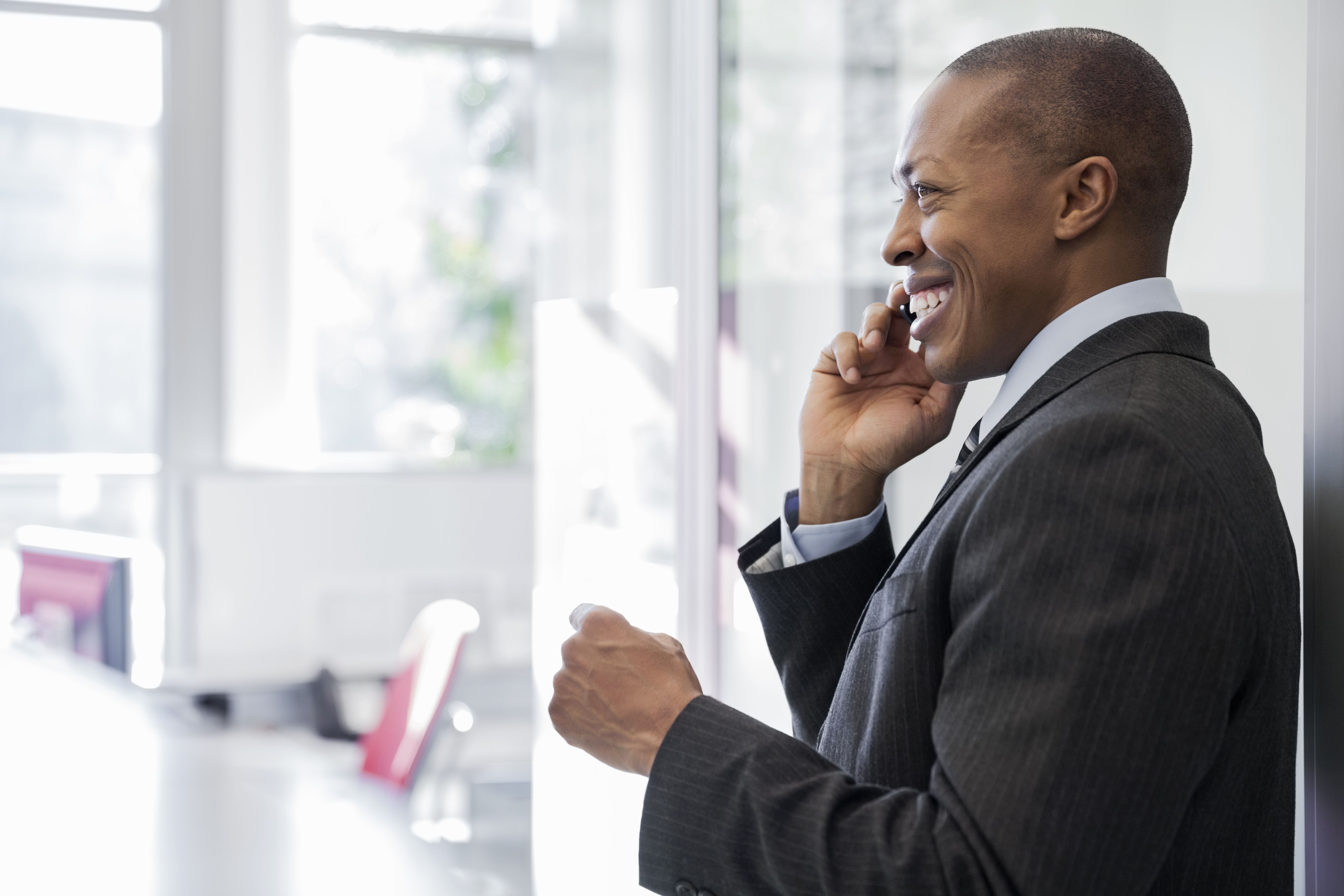 Smiling businessman talking on mobile phone in office