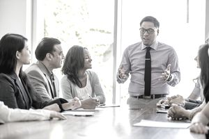 Man standing at conference table gives presentation to colleagues