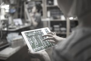 Close up female engineer examining digital circuit board on digital tablet