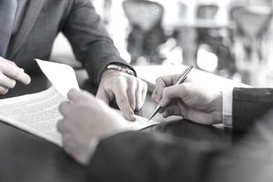 Businessman showing client where to sign document
