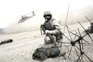 A combat soldier on the field communicates with a Pavehawk helicopter flying in the background.