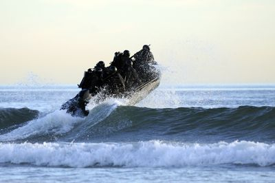 Students in Navy SEALs qualification training navigate the surf off the cost of Coronado.