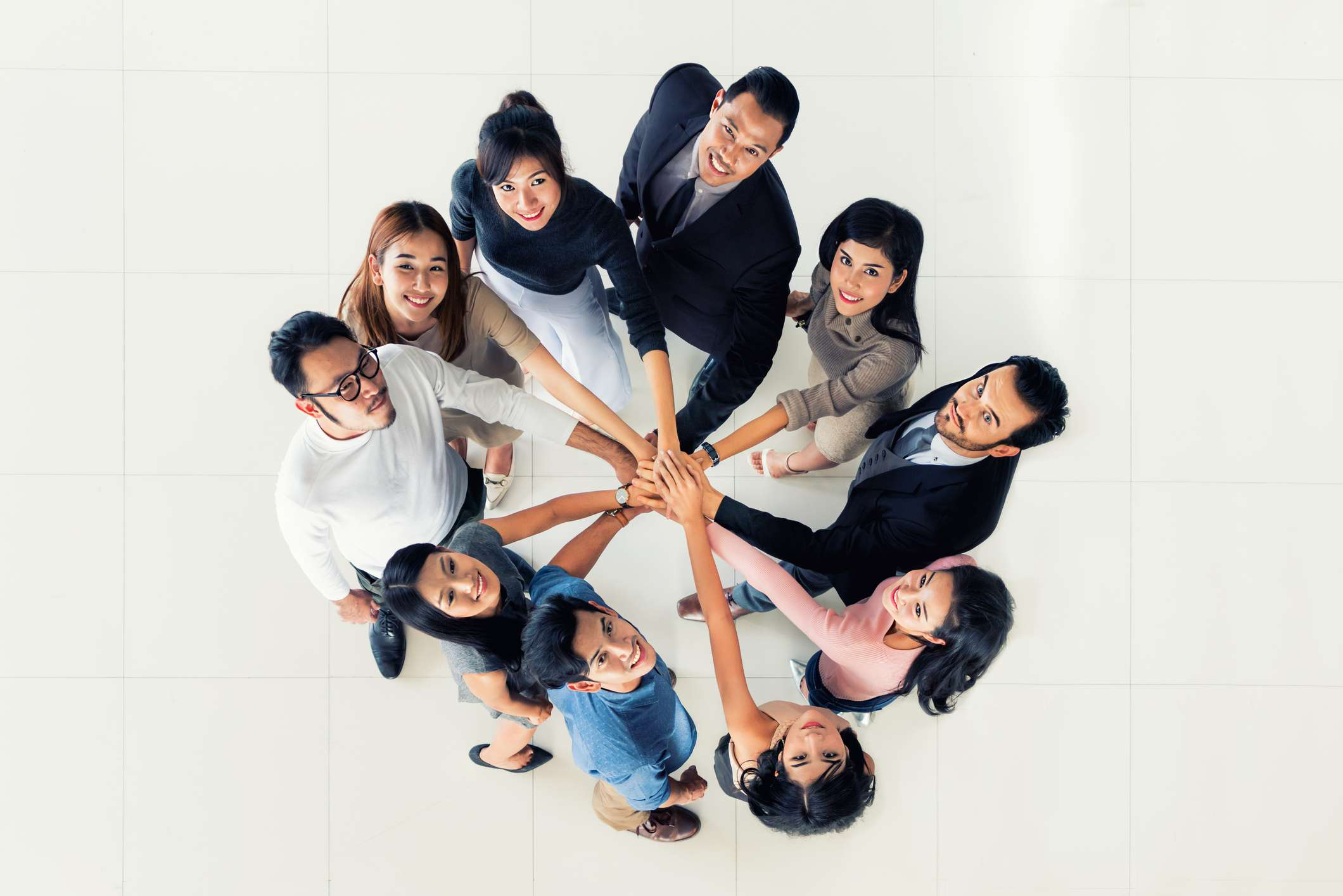 Coworkers standing in a circle with their hands in a pile in the center.