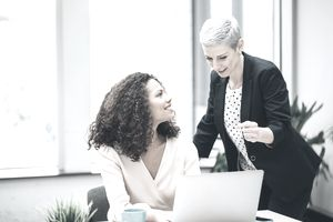 Young woman and older woman talking at work desk