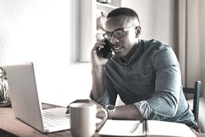 Young businessman networking in his home office.