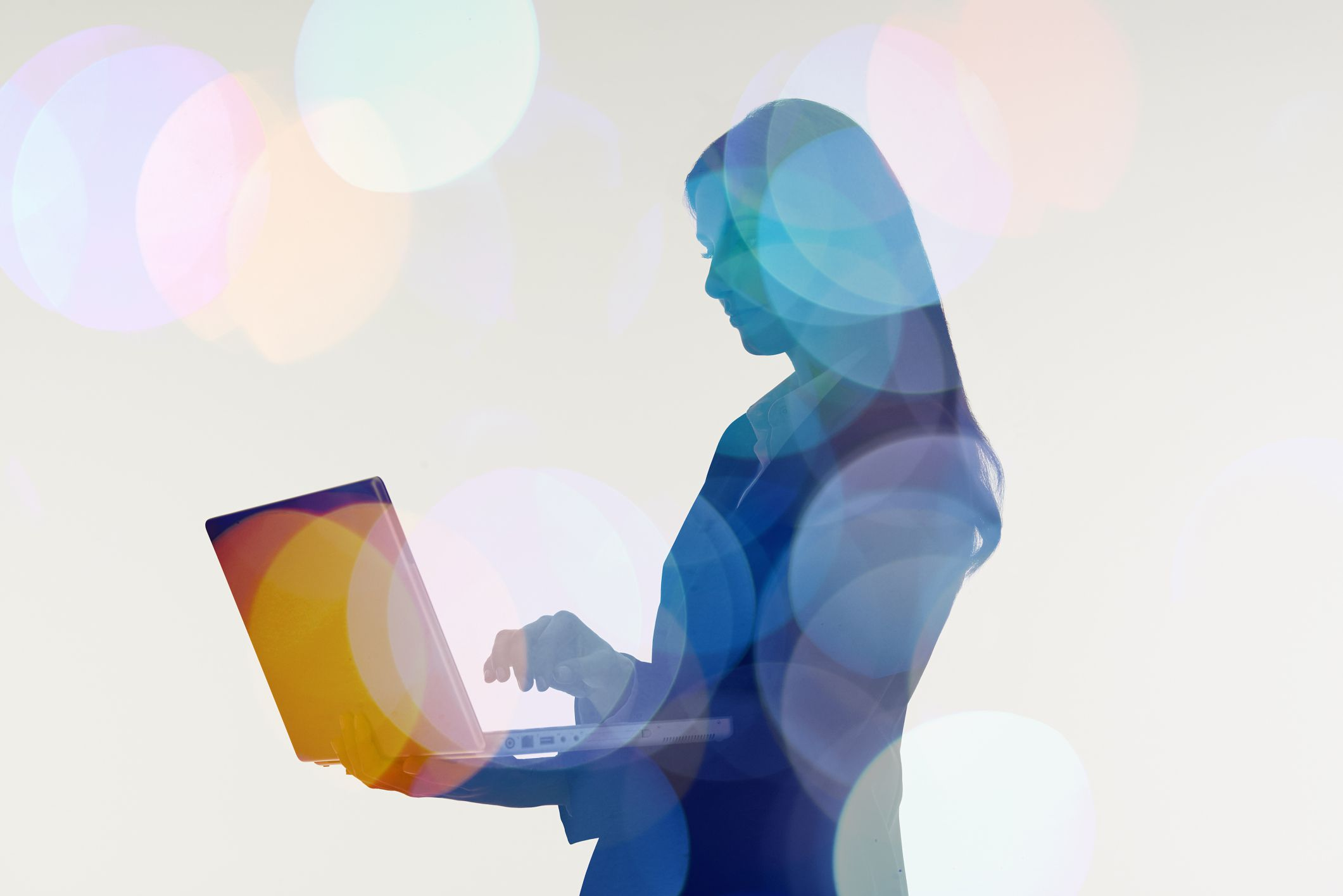 Businesswoman using laptop computer.Abstract colour effect.
