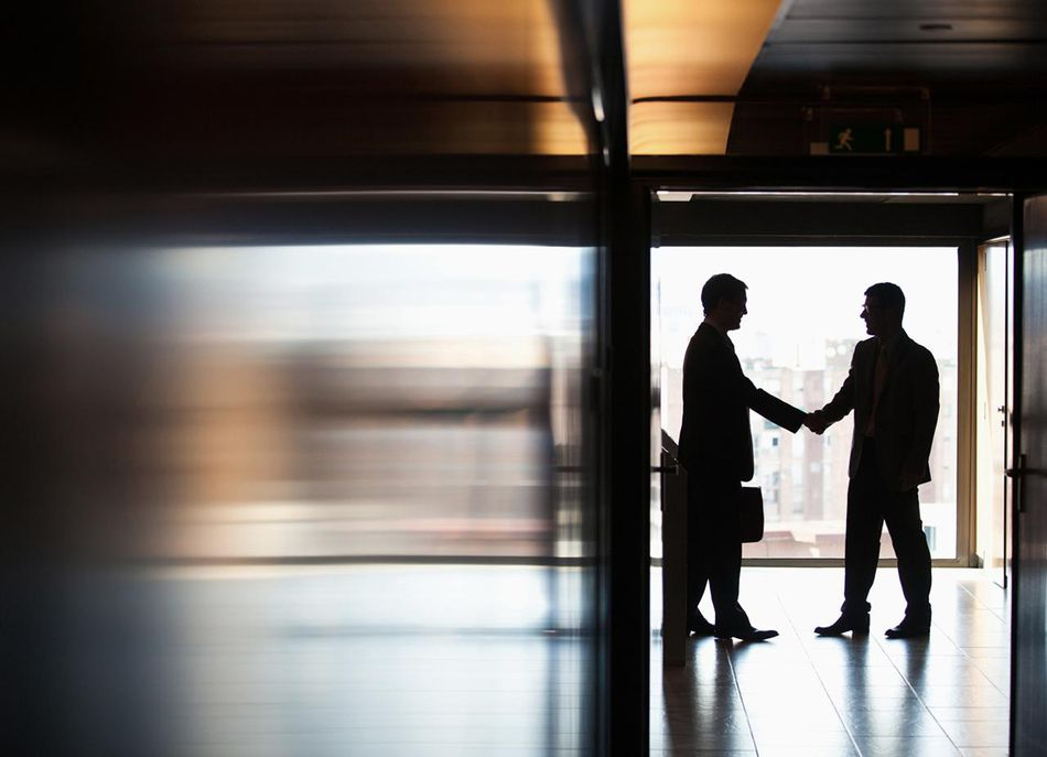 Businessmen shaking hands in corridor