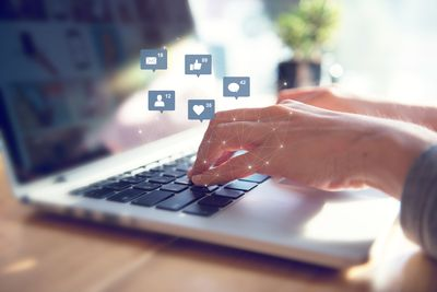 Businesswoman hands using laptop with icon social media and social network.