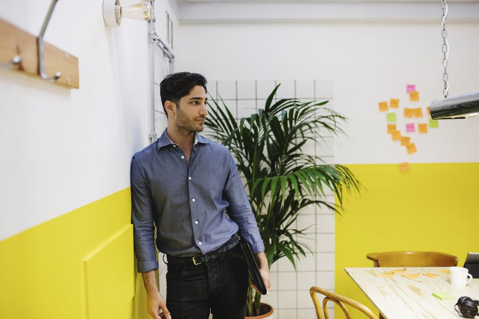 Thoughtful young man leaning on wall in creative office