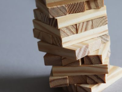 Wooden Jenga blocks stacked unevenly, representing the precarious balance between work and life.