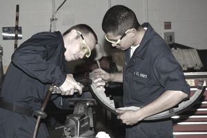 Two Navy construction mechanics working with machinery