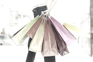 Woman walking in the mall with her hand full of shopping bags.