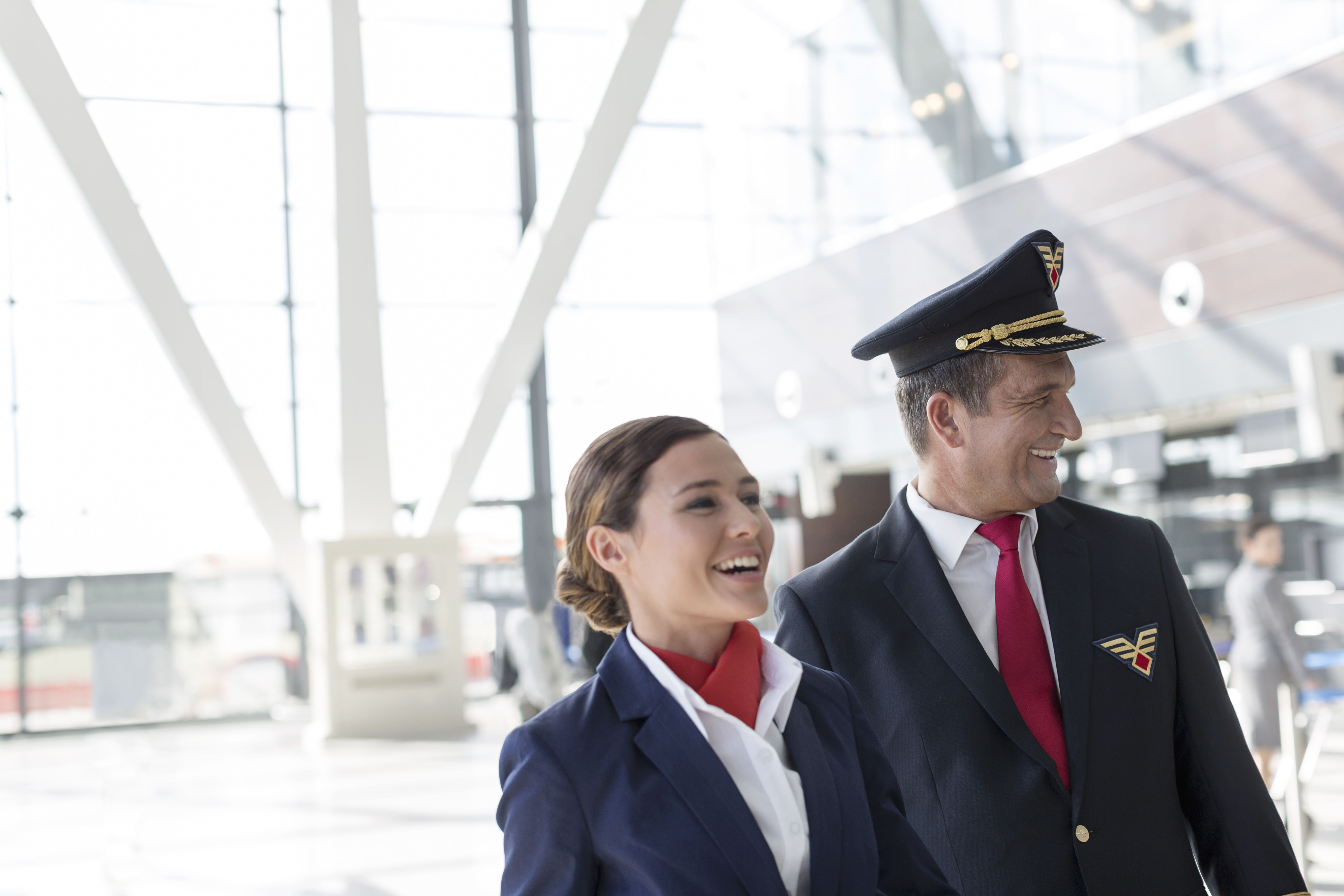Smiling pilot and flight attendant at the airport