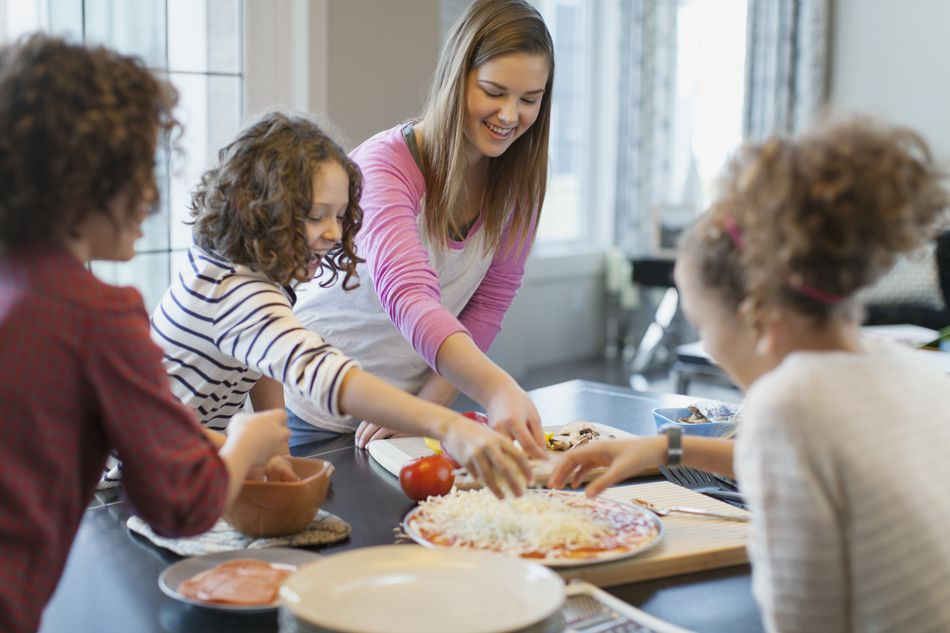 Girls having fun making pizza with babysitter.