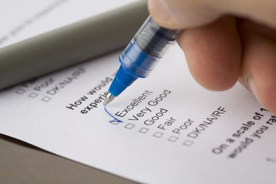 person filling out a questionnaire with a blue pen, check mark in corresponding