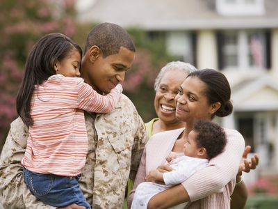 Solider and family in front of military housing