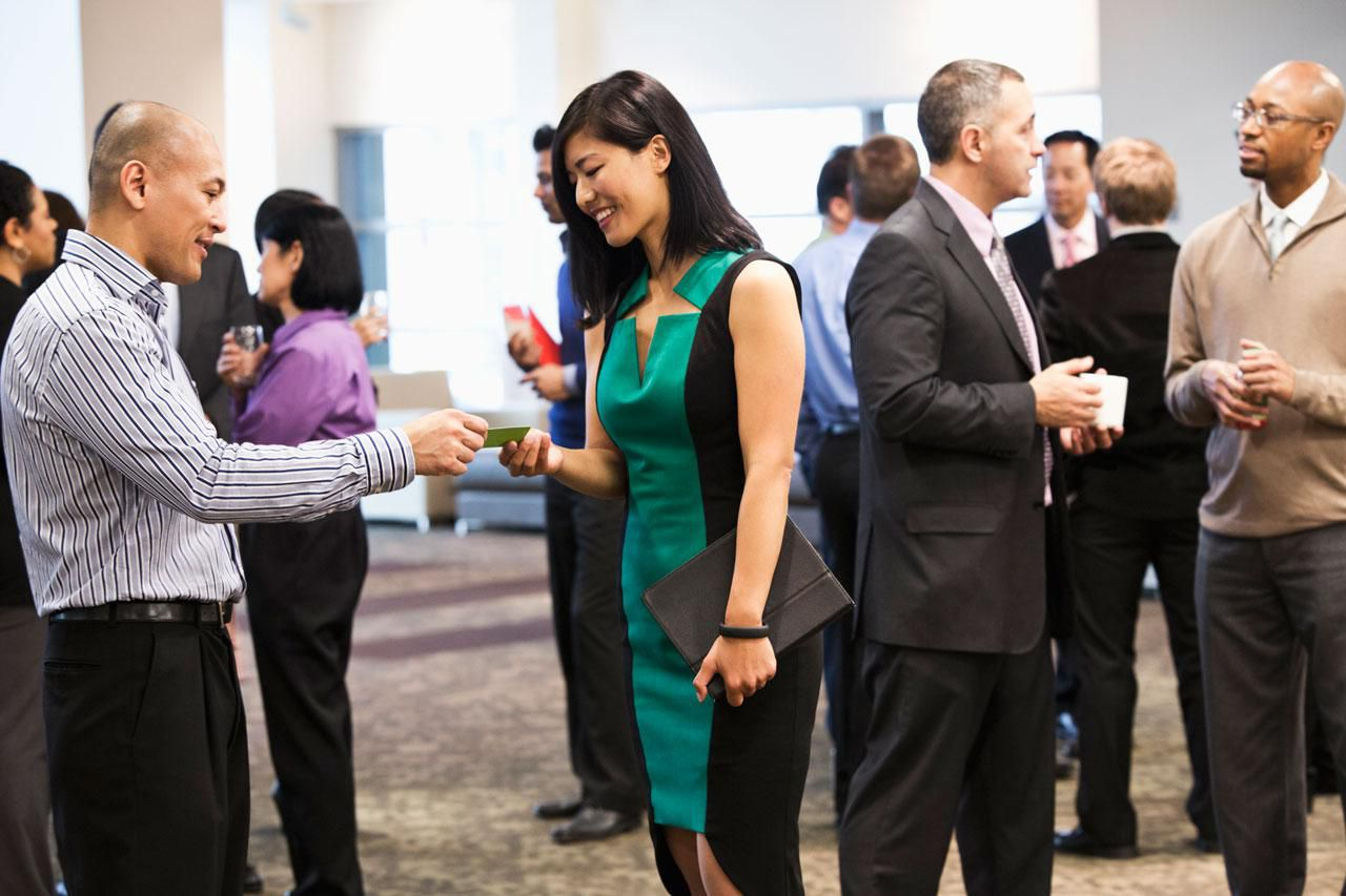 People at a networking event exchanging business cards.