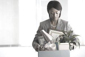 Businesswoman carrying box of personal items