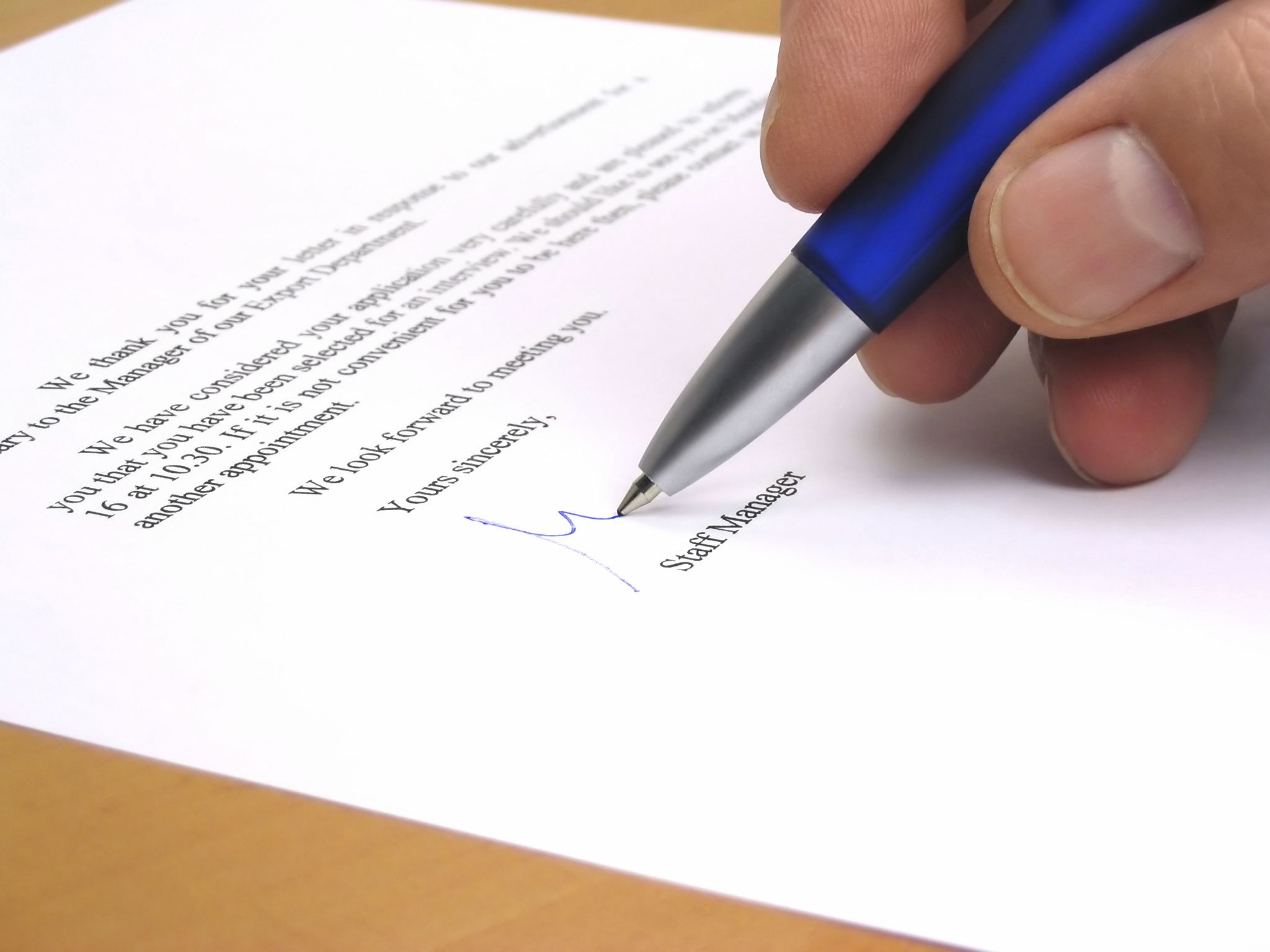 A person signing a business letter.