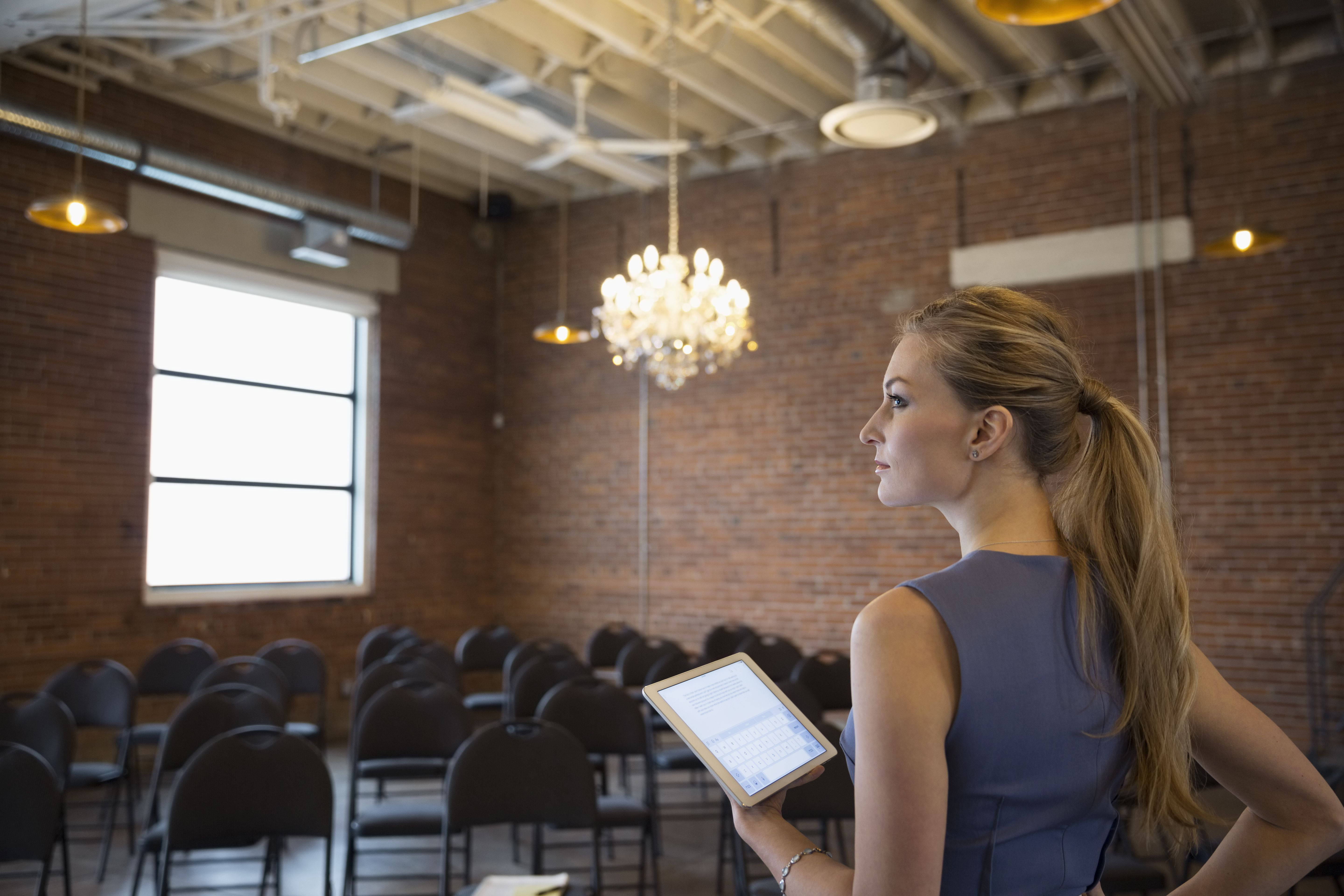 Ambitious businesswoman with digital tablet in conference room with chandelier