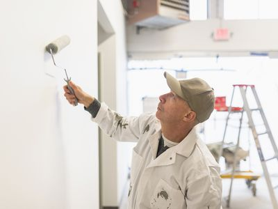 A skilled painter in overalls painting a wall using a roller brush.