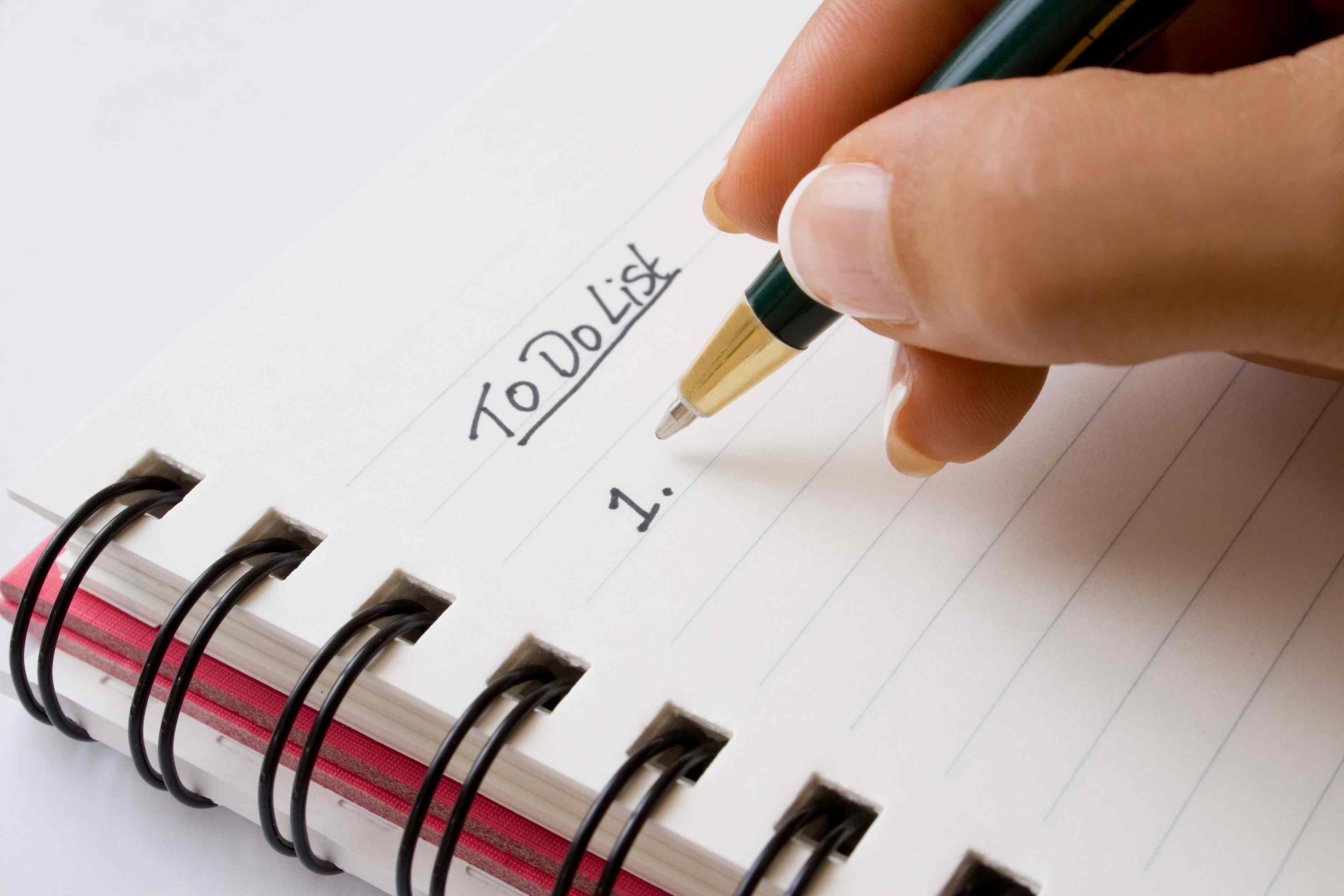 Close up of a woman's hand as she writes a to do list.
