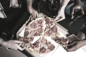 Four friends company eat fresh pizza at home