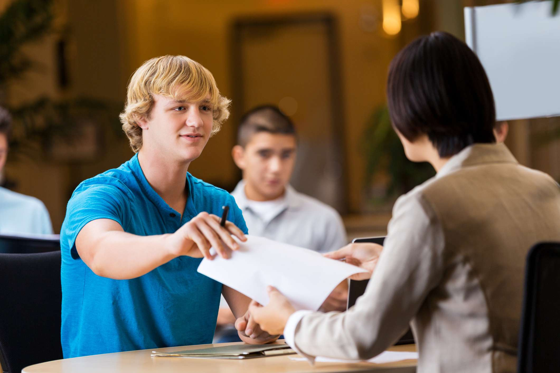 Young student handing paper to employer