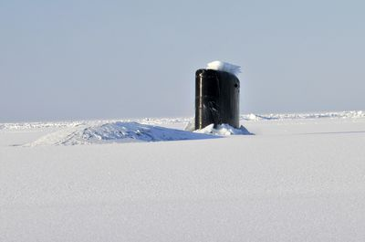 Navy submarine surfacing through an ice sheet in the Arctic during operations.