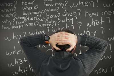 Businessman staring at a chalkboard with many questions