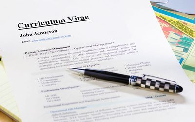 a curriculum vitae sits on a desk for review