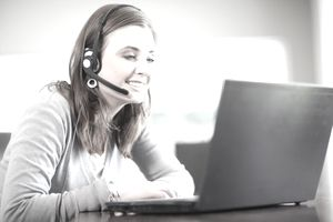 Woman with headset and laptop providing virtual technical support