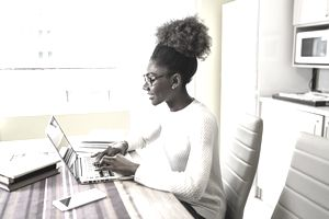 Woman at home on laptop researching and job searching