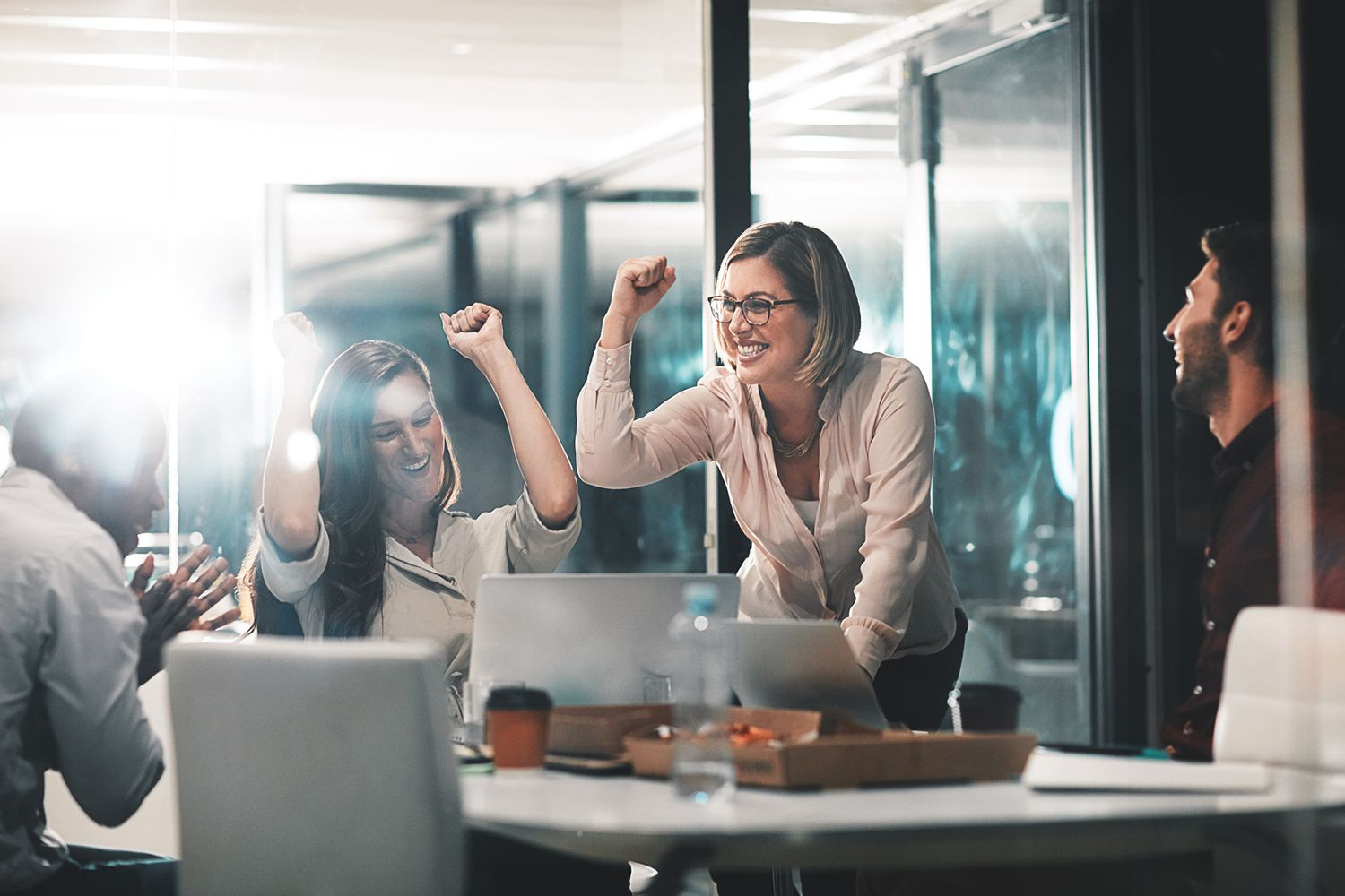Team of co-workers celebrating in conference room
