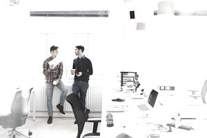 Two creatives chatting in open plan office
