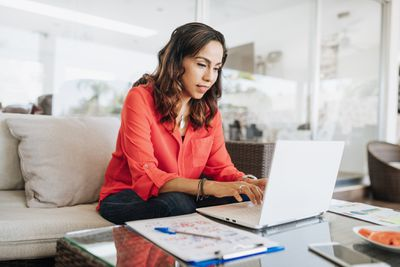 Woman wearing jeans and button-down shirt working on a laptop with a notepad and pen beside her.