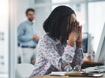 Woman looking stressed at her desk in the office