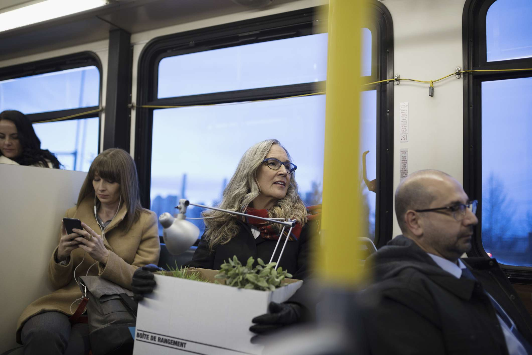 Laid-off businesswoman commuter riding bus with box of belongings