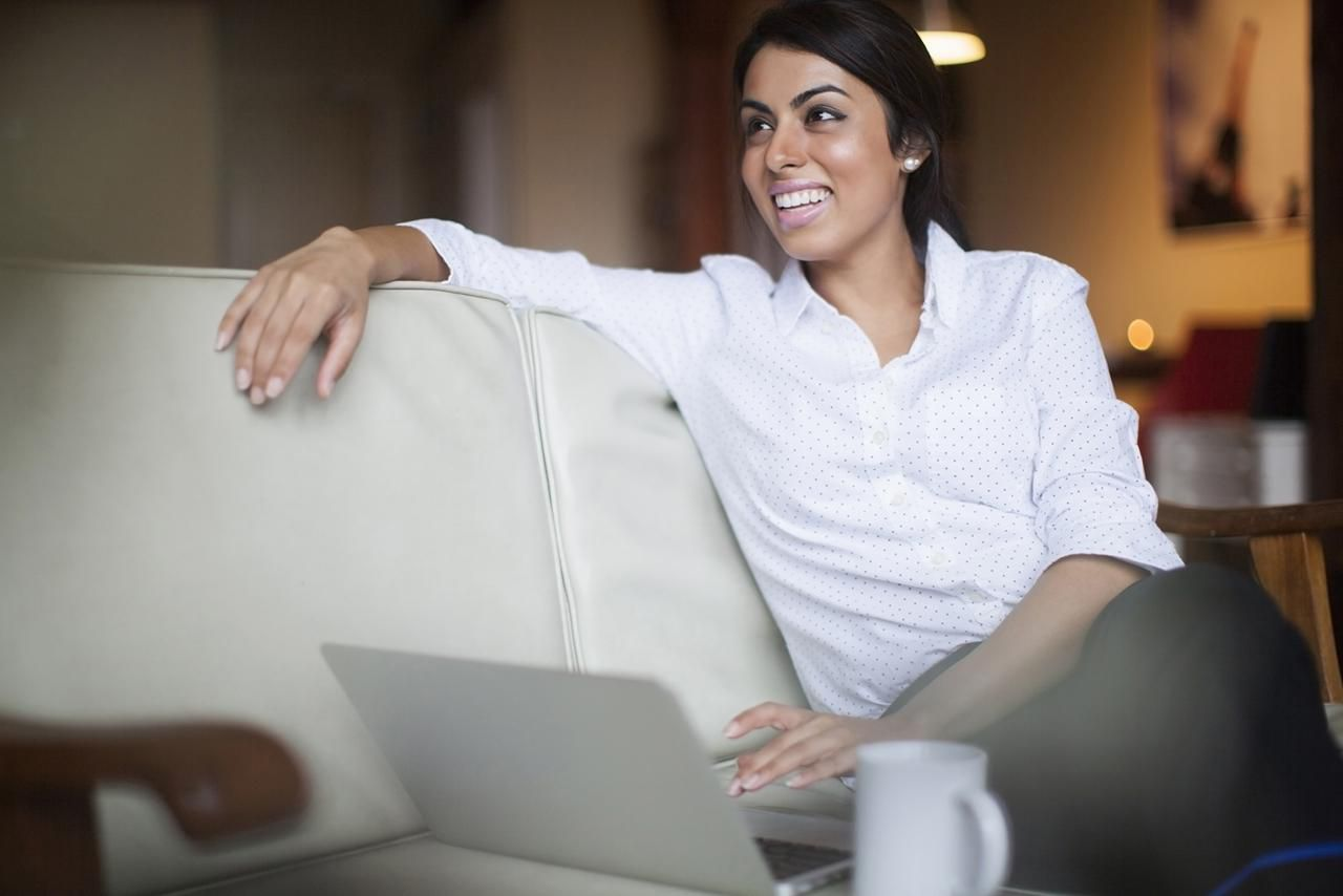 Woman smiling and using a laptop computer on couch