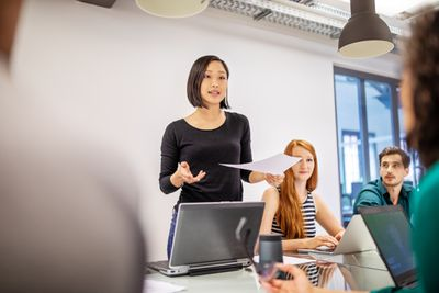 Woman discussing report with colleagues in a meeting