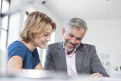 Woman and man smile at their work in a bright office.