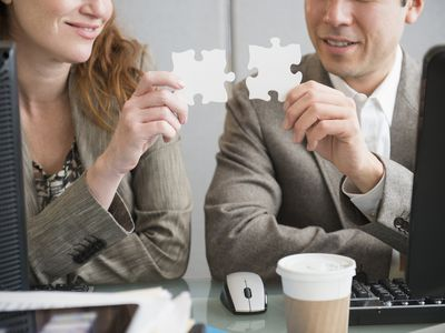 Two people with over-sized puzzle pieces putting them together to determine if they are a good fit.