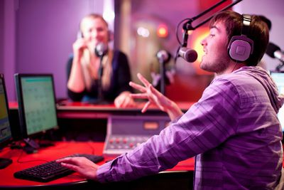 A photo of a man and woman announcing a radio program from a studio.