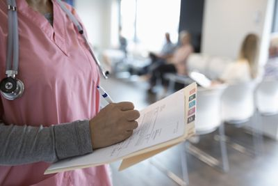 Close up female nurse writing on medical record in clinic waiting room